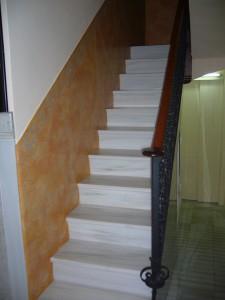 Vista de la escalera y detalle del estucado al fuego del zócalo